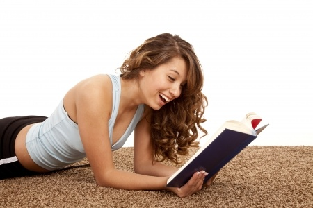 Female laying on her stomach reading a book she is laughing at